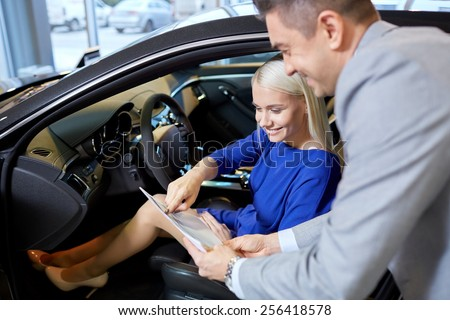 auto business, car sale, consumerism and people concept - happy woman with car dealer in auto show or salon - stock photo