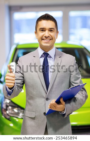 auto business, car sale, consumerism, gesture and people concept - happy man showing thumbs up at auto show or salon - stock photo