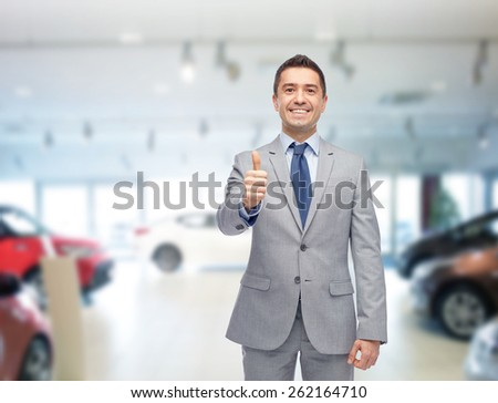 auto business, car sale, consumerism, gesture and people concept - happy man showing thumbs up over auto show or salon background - stock photo