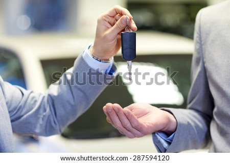 auto business, car sale, deal and people concept - close up of male hands with car key in auto show or salon - stock photo