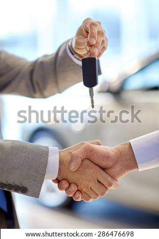 auto business, car sale, deal, gesture and people concept - close up of dealer giving key to new owner and shaking hands in auto show or salon - stock photo