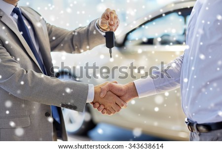 auto business, car sale, deal, gesture and people concept - close up of dealer giving key to new owner and shaking hands in auto show or salon over snow effect - stock photo