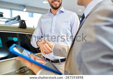 auto business, car sale, deal, gesture and people concept - close up of happy man and car dealer with tablet pc computer shaking hands in auto show or salon - stock photo