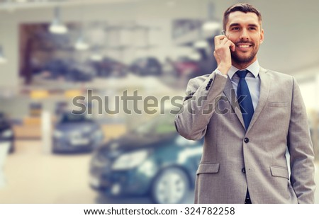 auto business, car sale, gesture and people concept - smiling businessman talking on smartphone over auto show background - stock photo