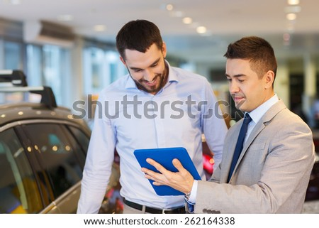 auto business, car sale, technology and people concept - happy man and car dealer with tablet pc computer in auto show or salon - stock photo