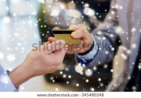 auto business, sale and people concept - close up of customer hand giving credit card to car dealer in auto show or salon over snow effect - stock photo
