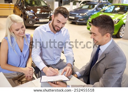 auto business, sale and people concept - happy couple with dealer buying car and signing documents in auto show or salon - stock photo