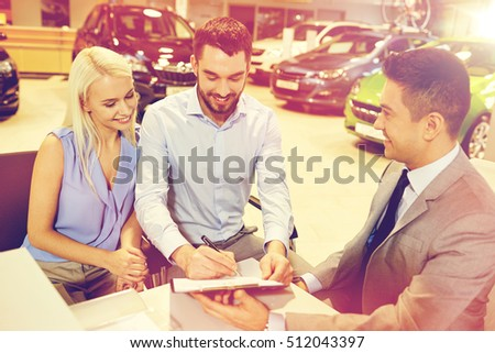auto business, sale and people concept - happy couple with dealer buying car and signing documents in auto show or salon