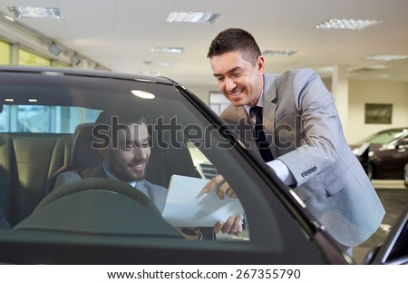 auto business, sale and people concept - happy man with dealer buying car in auto show or salon - stock photo