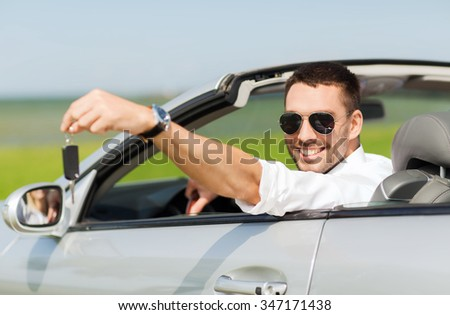 auto business, transport, leisure and people concept - happy man in cabriolet showing car key - stock photo