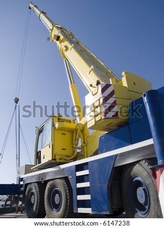 Auto-crane unloading against a blue sky - stock photo