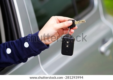 Auto dealership concept. Close-up view of car keys in the female hand - stock photo