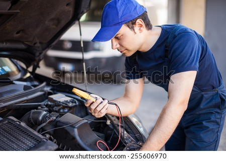 Auto electrician troubleshooting a car engine - stock photo