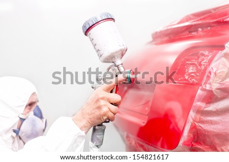 auto engineer painting a red paint on modern car in special booth