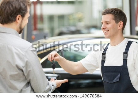 Auto mechanic and customer. Cheerful auto mechanic giving a car key to customer and smiling - stock photo
