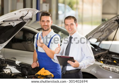 Auto mechanic and technician posing at camera in repair shop.