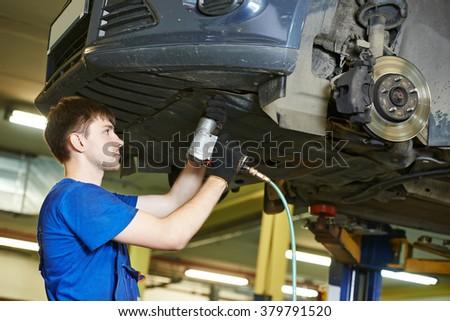 auto mechanic at car suspension repairing - stock photo
