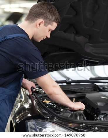 Auto mechanic at work. Confident auto mechanic working on car engine - stock photo