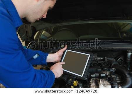 Auto mechanic by car with open hood using digital tablet - stock photo