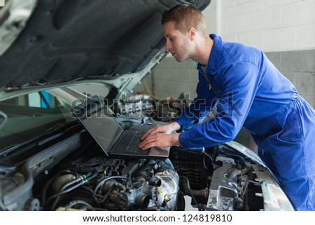 Auto mechanic by car working on laptop