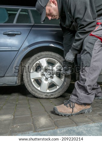 Auto mechanic changing rear tire in passenger car
