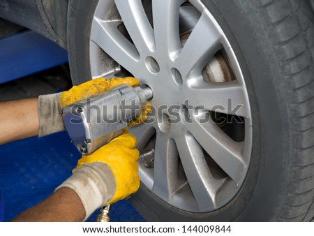 Auto mechanic changing wheel on car with pneumatic wrench - stock photo