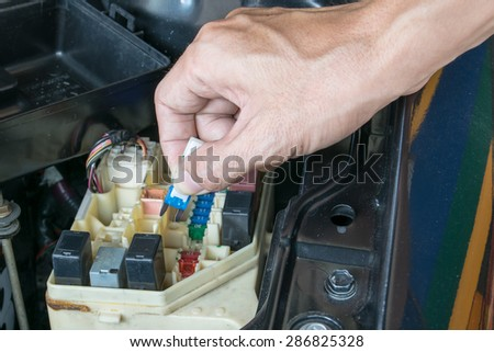 Auto mechanic checking a car fuse - stock photo