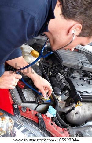 Auto mechanic checking a vehicle. Car repair service. - stock photo