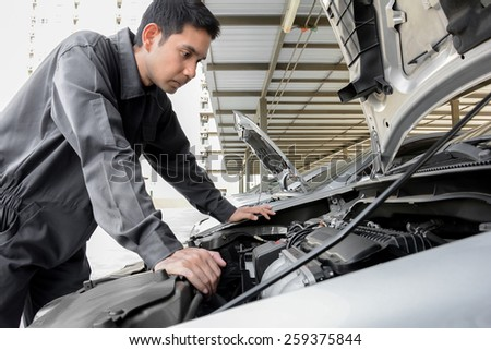 Auto mechanic checking car engine at the garage - soft focus - stock photo