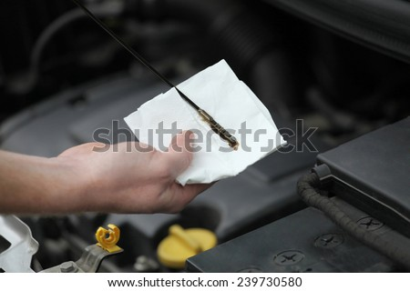 Auto mechanic checking engine oil dipstick in car. Auto mechanic in car repair