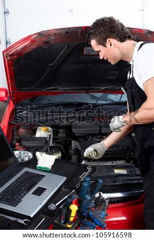 Auto mechanic checking oil. Car repair service. - stock photo