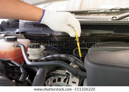 Auto mechanic checking oil level in a car engine