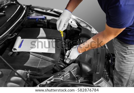 Auto mechanic checking the oil level in car engine