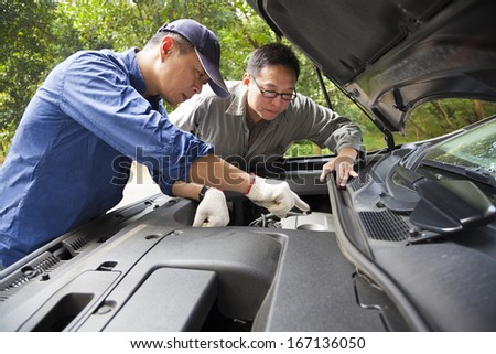 Auto mechanic fixes a car in service - stock photo