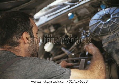 Auto Mechanic Fixing Car In A Workshop - stock photo