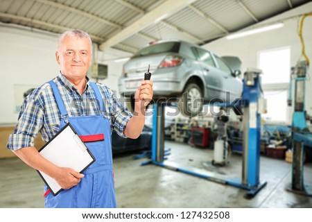 Auto mechanic holding a car key at auto repair shop during an automobile maintenance service - stock photo