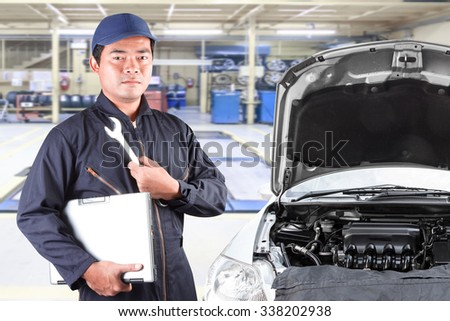 Auto mechanic holding computer and tool for service operation repaired at maintenance repair service station - stock photo