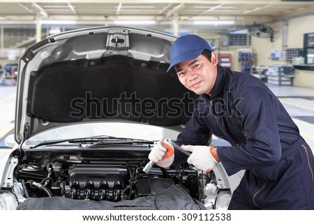 Auto mechanic holding wrench for working in garage repair service  - stock photo