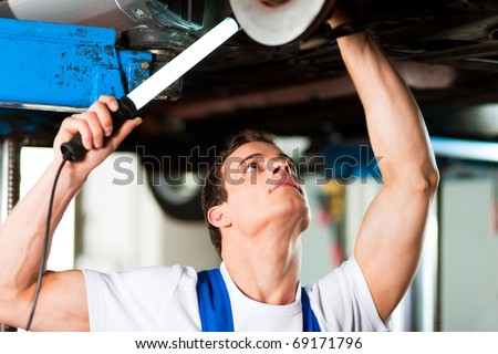 Auto mechanic in his workshop looking under a car on a hoist - stock photo