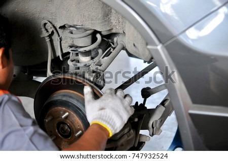 Auto mechanic in process of new tire replacement, Car brake repairing in garage, Brakes on a car with removed wheel, car brake part at garage,car brake disc without wheels closeup