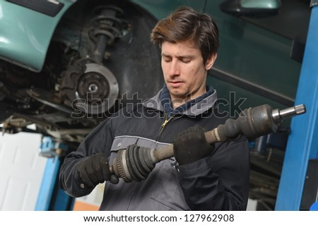 Auto Mechanic  is working in car repair shop. - stock photo