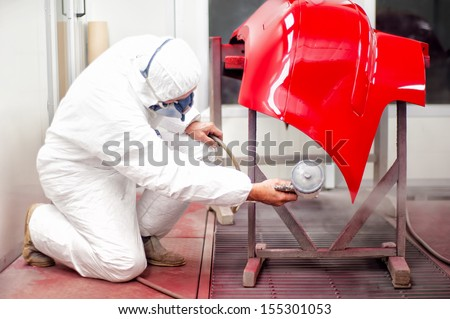 Auto mechanic painting with spray gun bumper of car in special booth