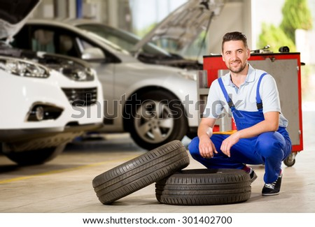 Auto mechanic posing at camera with tire. - stock photo