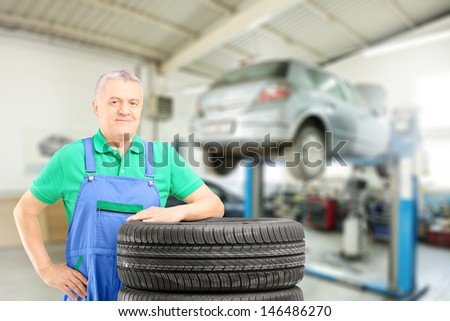 Auto mechanic posing on tires in front of car during automobile maintenance at auto repair shop - stock photo