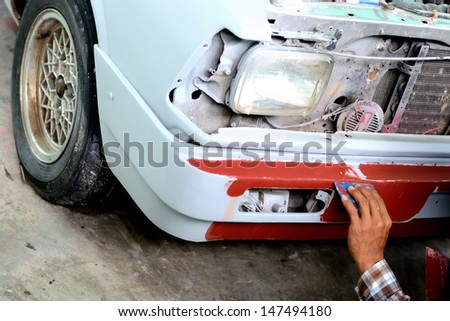 Auto mechanic preparing the front bumper of a car for painting  - stock photo