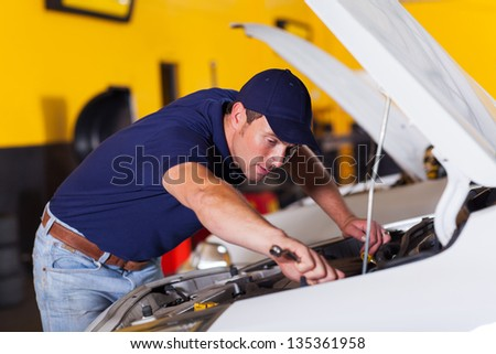 auto mechanic repairing vehicle inside workshop - stock photo