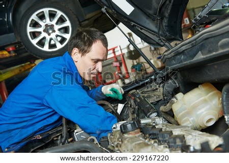 auto mechanic repairman examining automobile car engine at maintenance repair service station garage - stock photo