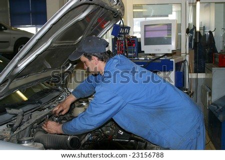 auto mechanic repairs a motor of the automobile - stock photo