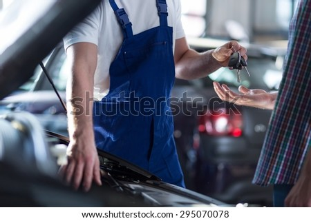 Auto mechanic's hands giving a car keys - stock photo