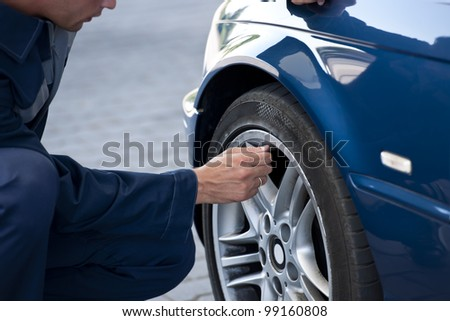 Auto mechanic/Service station worker  reviews necessary repairs or inflating - stock photo